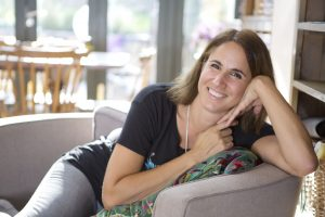 Picture is of author Sarah Sultoon half lying on a sofa with hands up to face